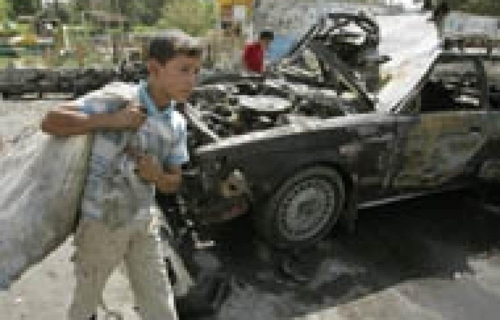 Un garçon ramassait hier des débris sur le site d'un attentat qui a tué deux soldats à Bagdad.