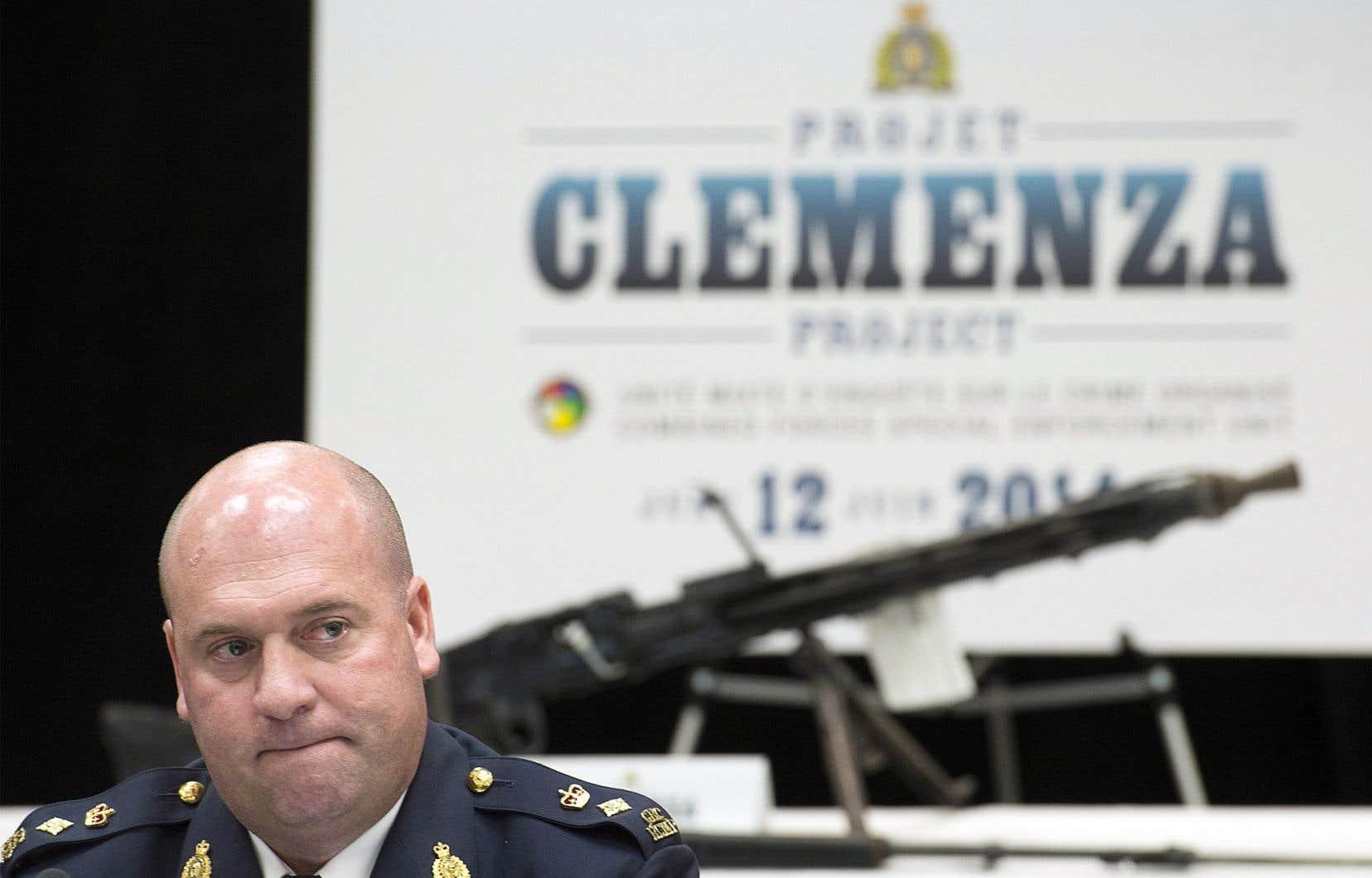Le surintendant Michel Arcand, de la GRC. En arrière-plan, l'une des armes saisies en cours d'enquête.