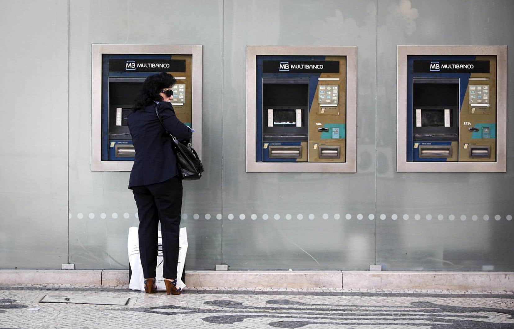 À Lisbonne, une cliente de la Banco Espirito Santo effectue une opération bancaire à un guichet automatique.