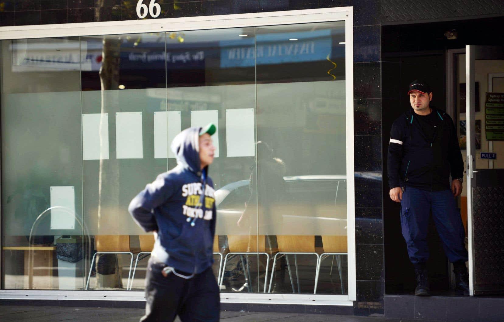 Un garde de sécurité observe les passants devant le Sydney Medically Supervised Injecting Centre, en Australie, qui offre divers services médicaux.