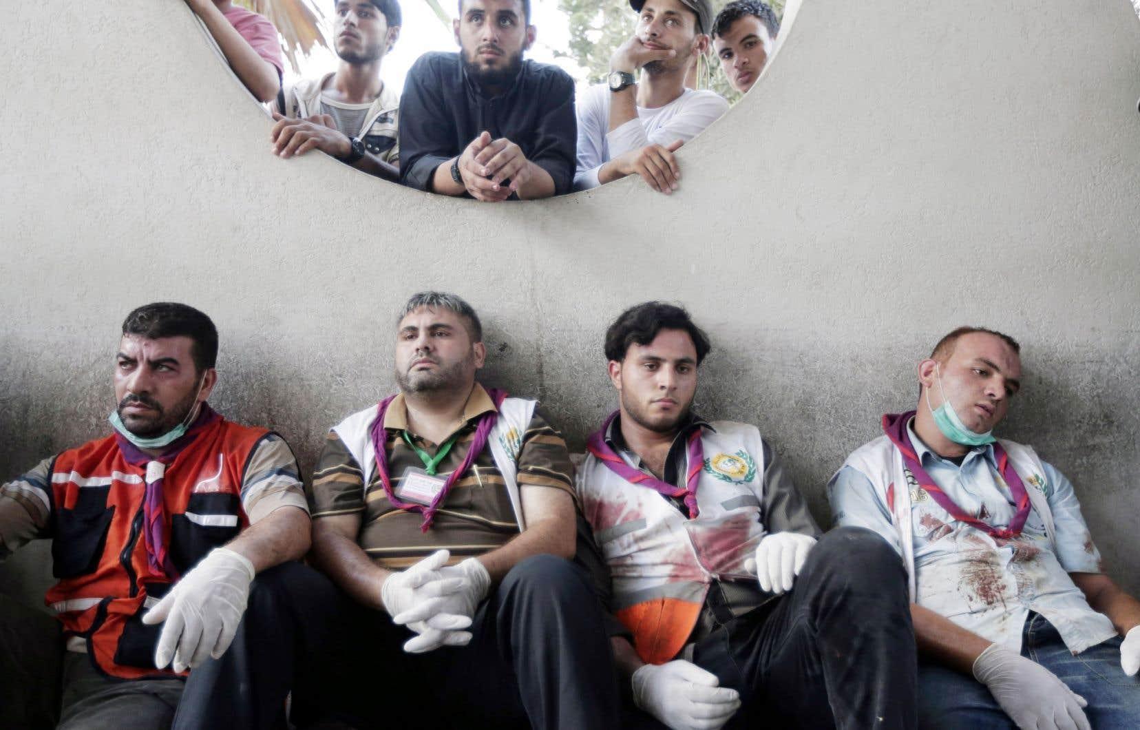 Au cœur d'une journée de cauchemar marquée par des tueries dans un marché et un centre de réfugiés de l'ONU, les ambulanciers palestiniens, appelés à chaque bombardement, exténués, font une pause à l'hôpital Shifa, de Gaza.