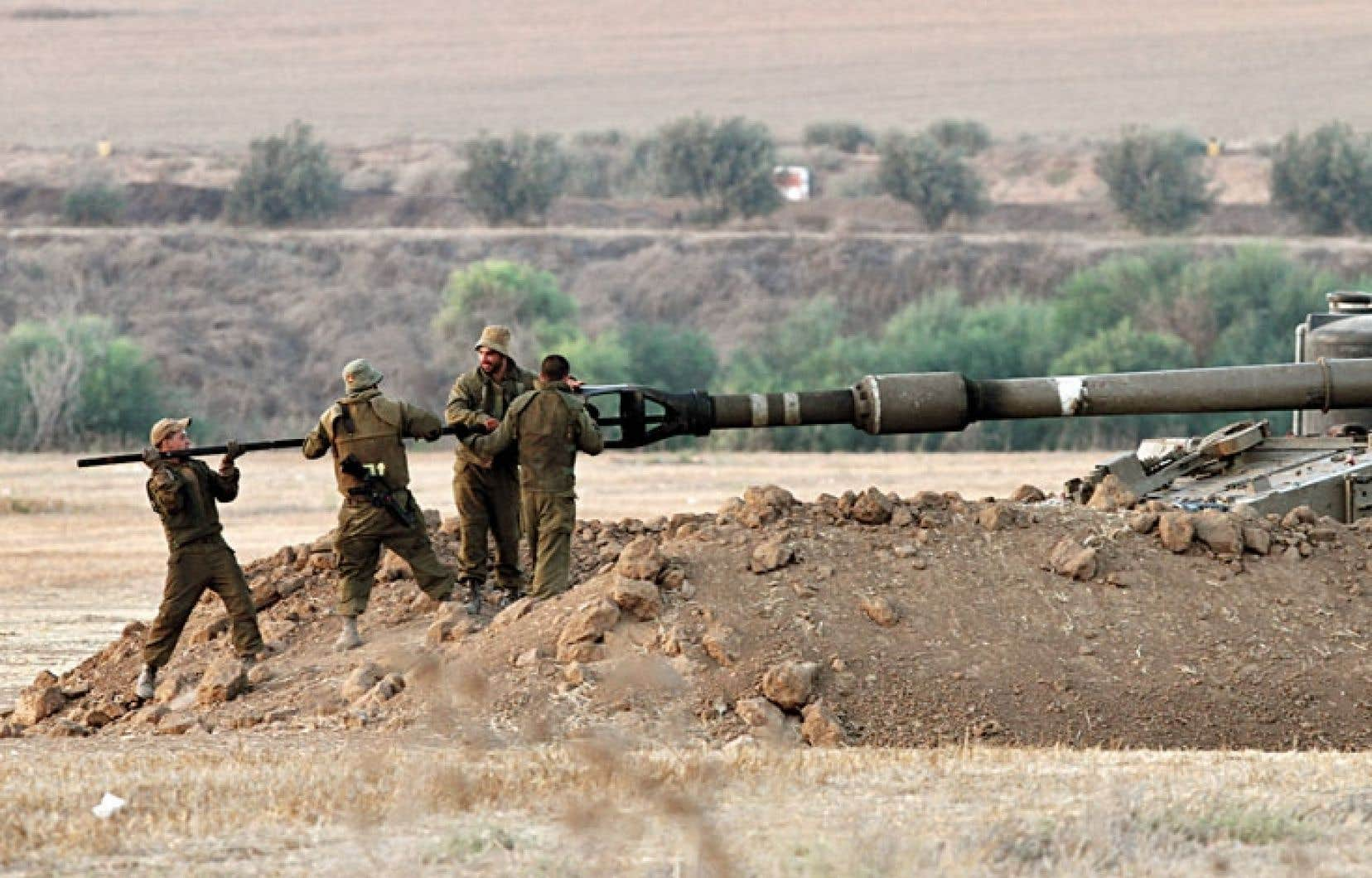 Des soldats israéliens nettoyaient le canon d'un char à la frontière avec Gaza, jeudi.