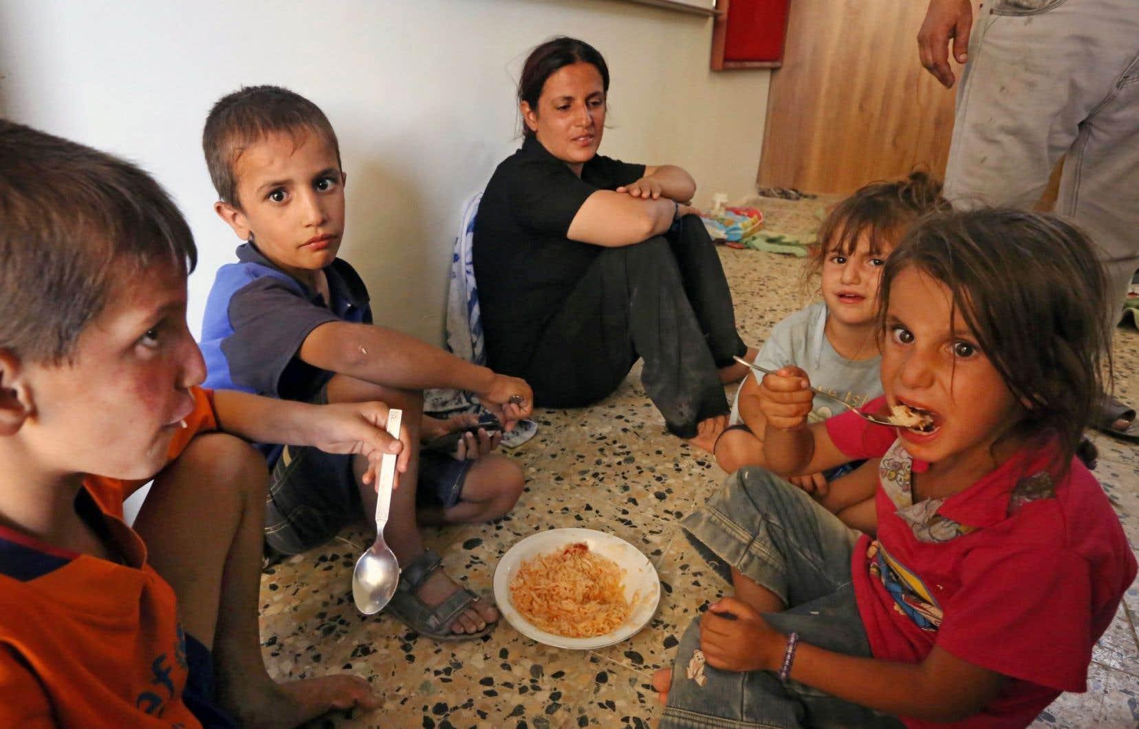Des chrétiens d'Irak se reposant, le 7 août, dans l'église Saint-Joseph du village kurde d'Arbil aprés avoir fui les violences de leur village.