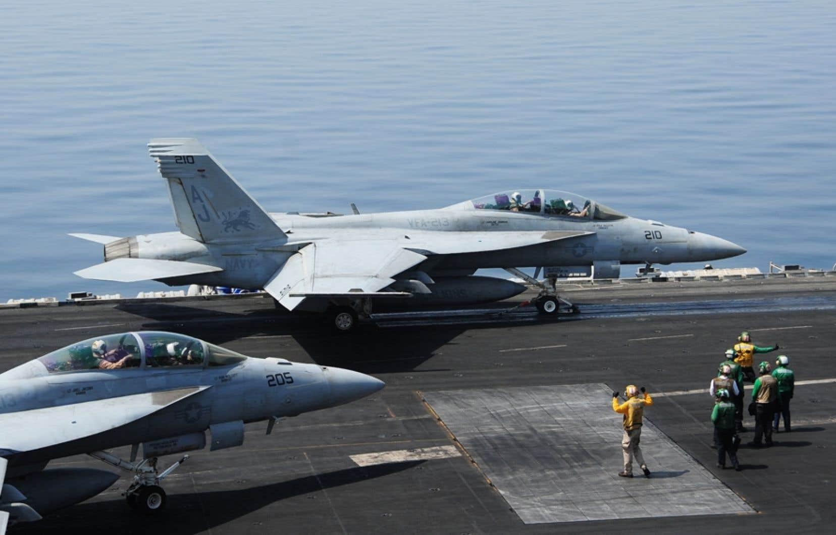 Des avions de chasses américains se déplacent sur le pont du porte-avion George H.W. Bush, dans le golfe Persique.