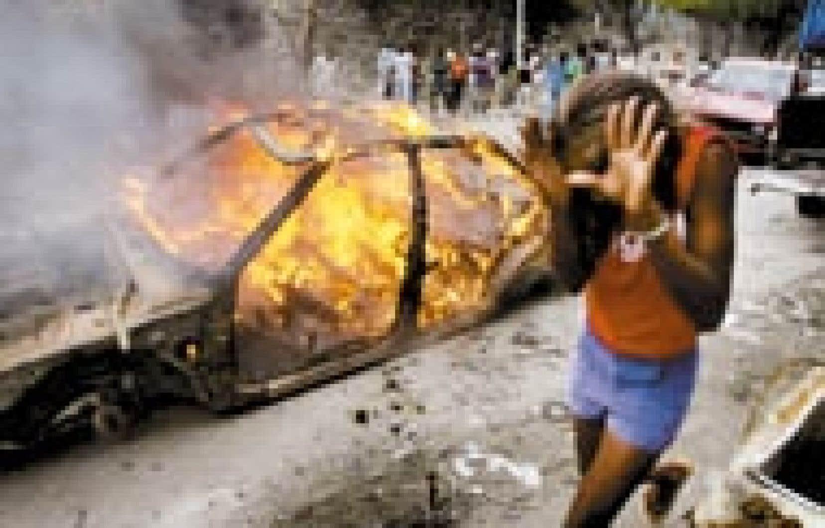 Une jeune fille se protège des flammes en passant près d'une des barricades érigées hier à Port-au-Prince par des partisans de l'ancien président René Préval. Un climat de violence s'est installé dans la capitale haïtienne où les résult