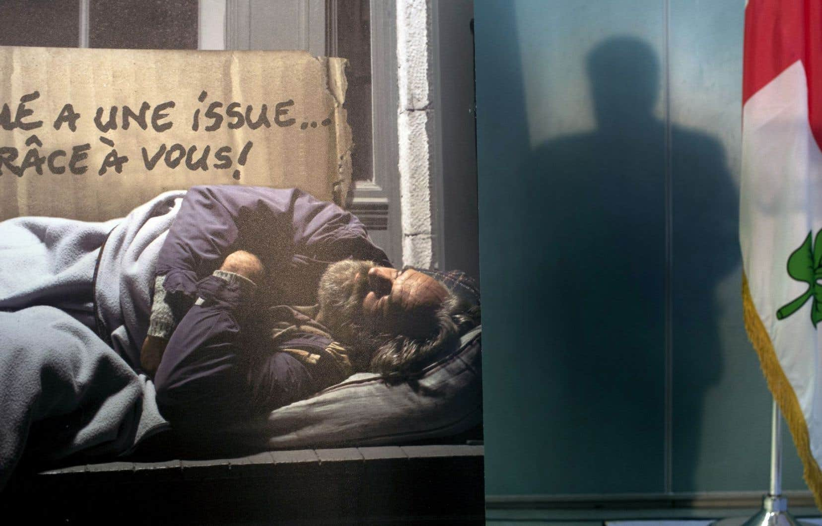 L'ombre du maire de Montréal, Denis Coderre, est projetée près d'une affiche pendant le dévoilement de son nouveau plan de lutte contre l'itinérance.