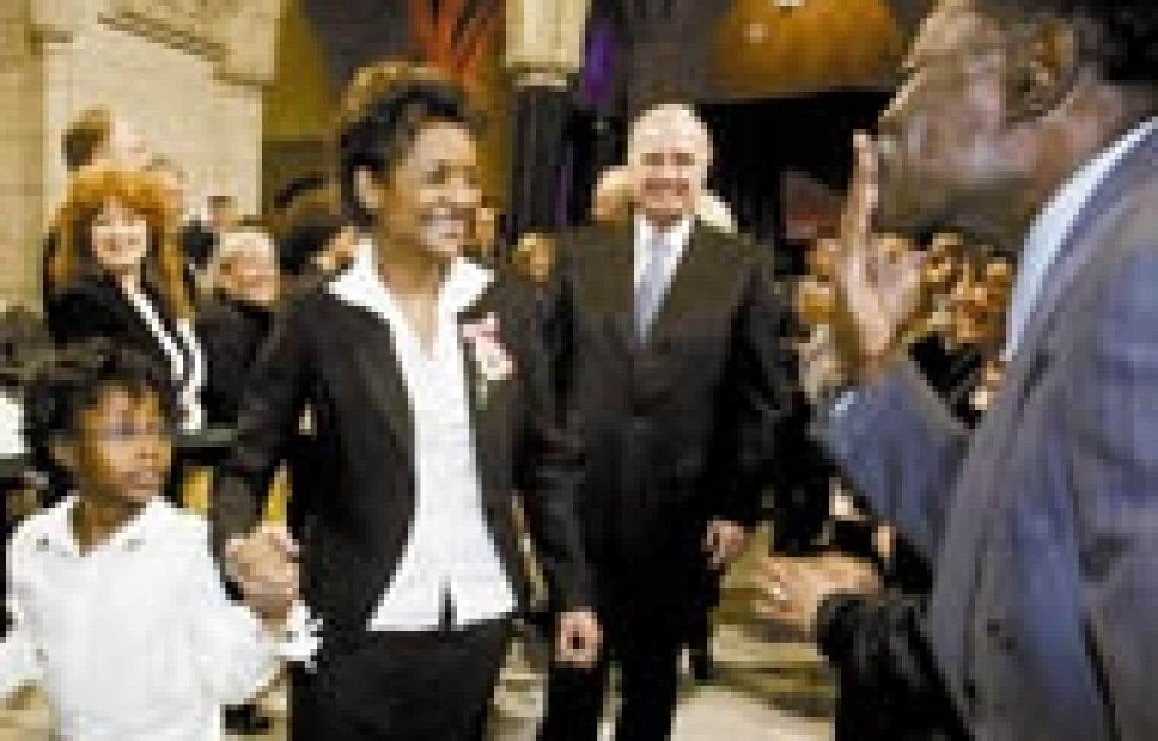 Michaëlle Jean, sa fille Marie-Éden et le premier ministre Paul Martin parmi la foule après la cérémonie d'installation de la nouvelle gouverneure générale, hier, à Ottawa. Des centaines de personnes, dont de nombreux représentants de la commu