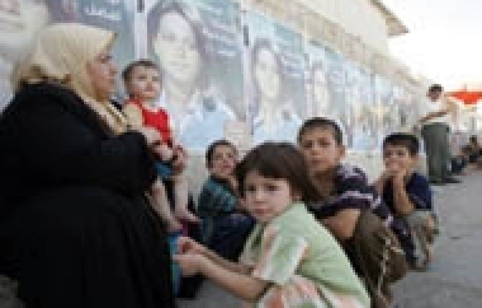 Pendant que les tractations sur la Constitution reprenaient hier, une famille irakienne s'est reposée devant un mur couvert d'affiches rappelant l'importance du document.