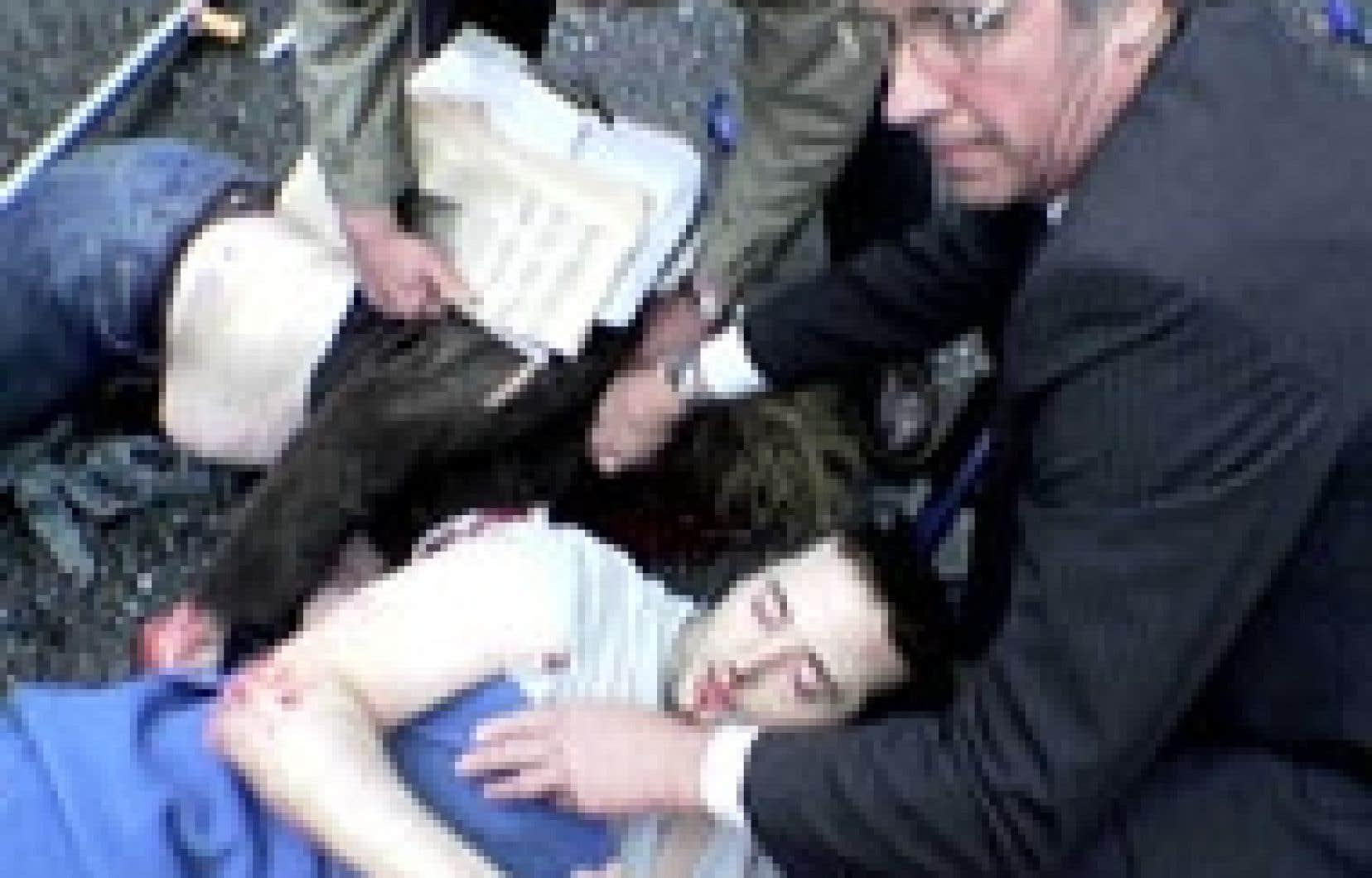 Des gens portent secours à des personnes blessées lors d'un des quatre attentats.