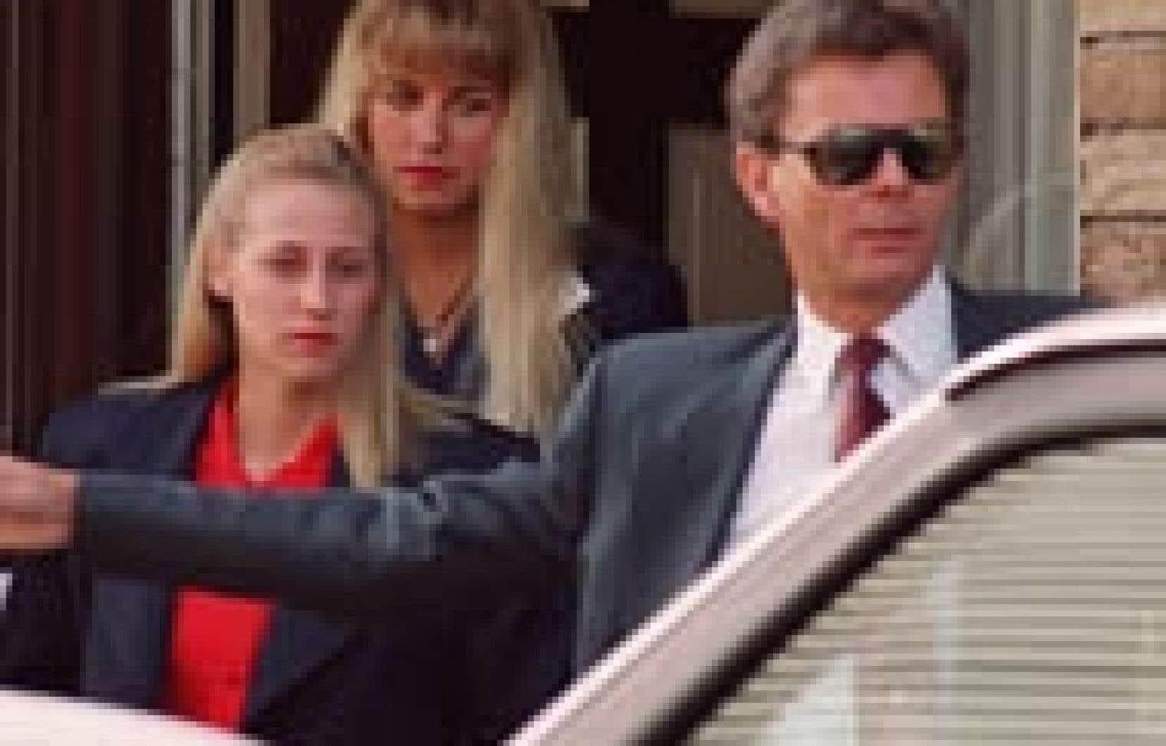 Karla Homolka (à l'arrière) est accompagnée de sa soeur Lori et d'un policier à la sortie de la maison familiale, le 30 juin 1993. Homolka se rendait au palais de justice pour y subir son procès pour le meurtre de Kristen French et de Leslie Mah