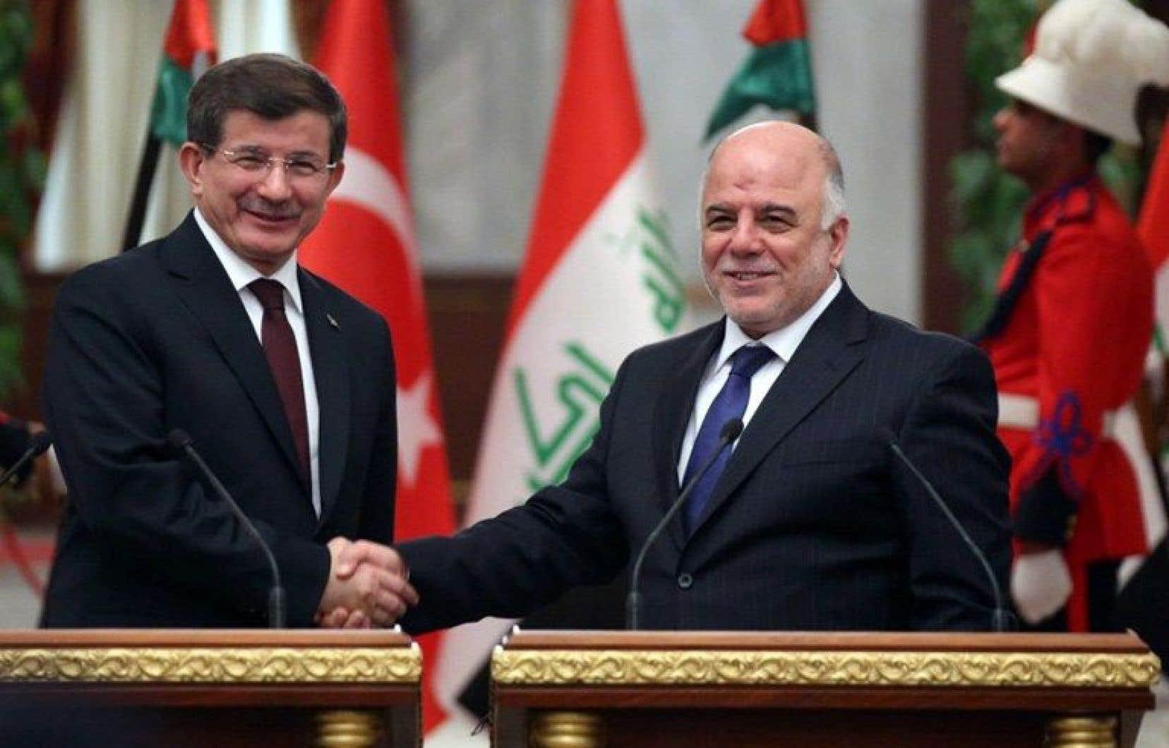 Le premier ministre turc Ahmet Davutoglu (gauche) et le chef du gouvernement irakien Haïdar al-Abadi, jeudi à Bagdad.