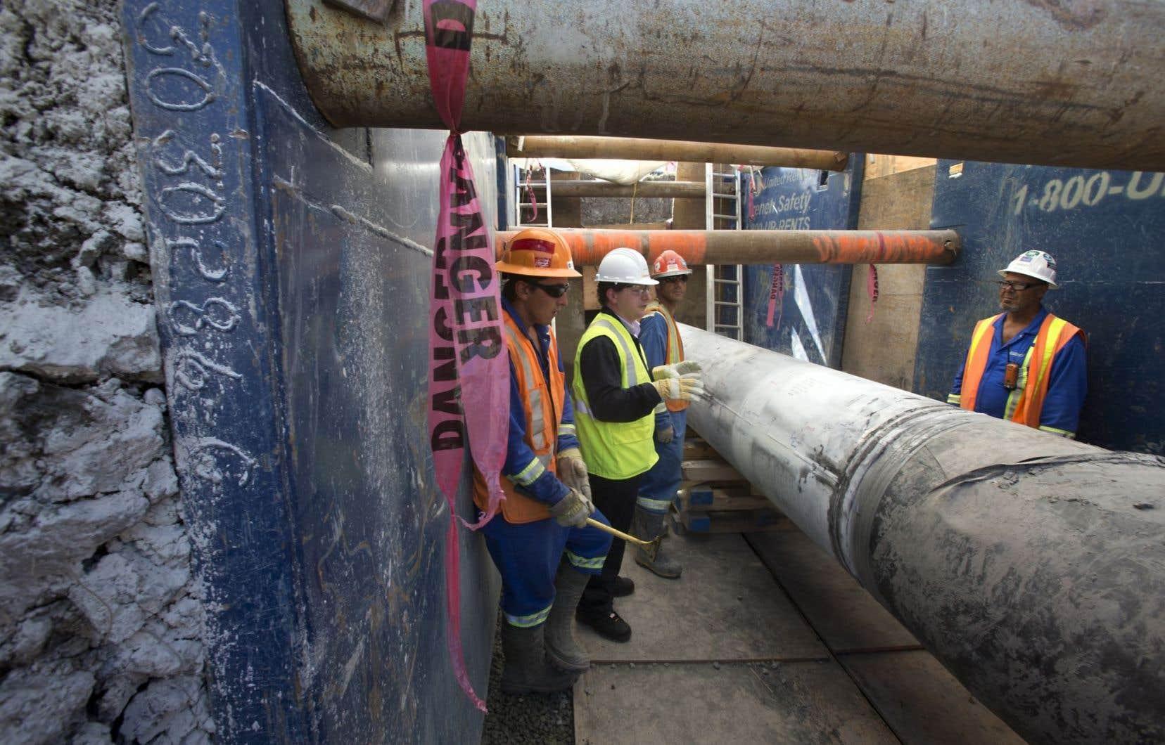 Des travailleurs examinent l'état de l'oléoduc 9B d'Enbridge.