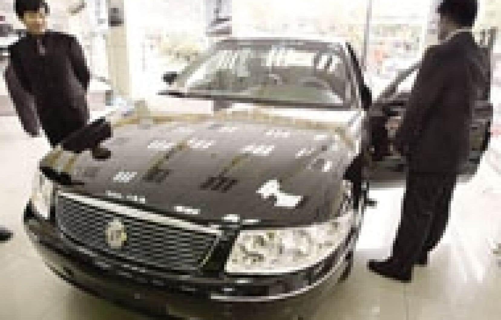 Des acheteurs chinois examinent un modèle de GM. Le constructeur automobile éprouve des difficultés en Asie, ce qui l'empêche de compenser les effets de la crise en Amérique du Nord.