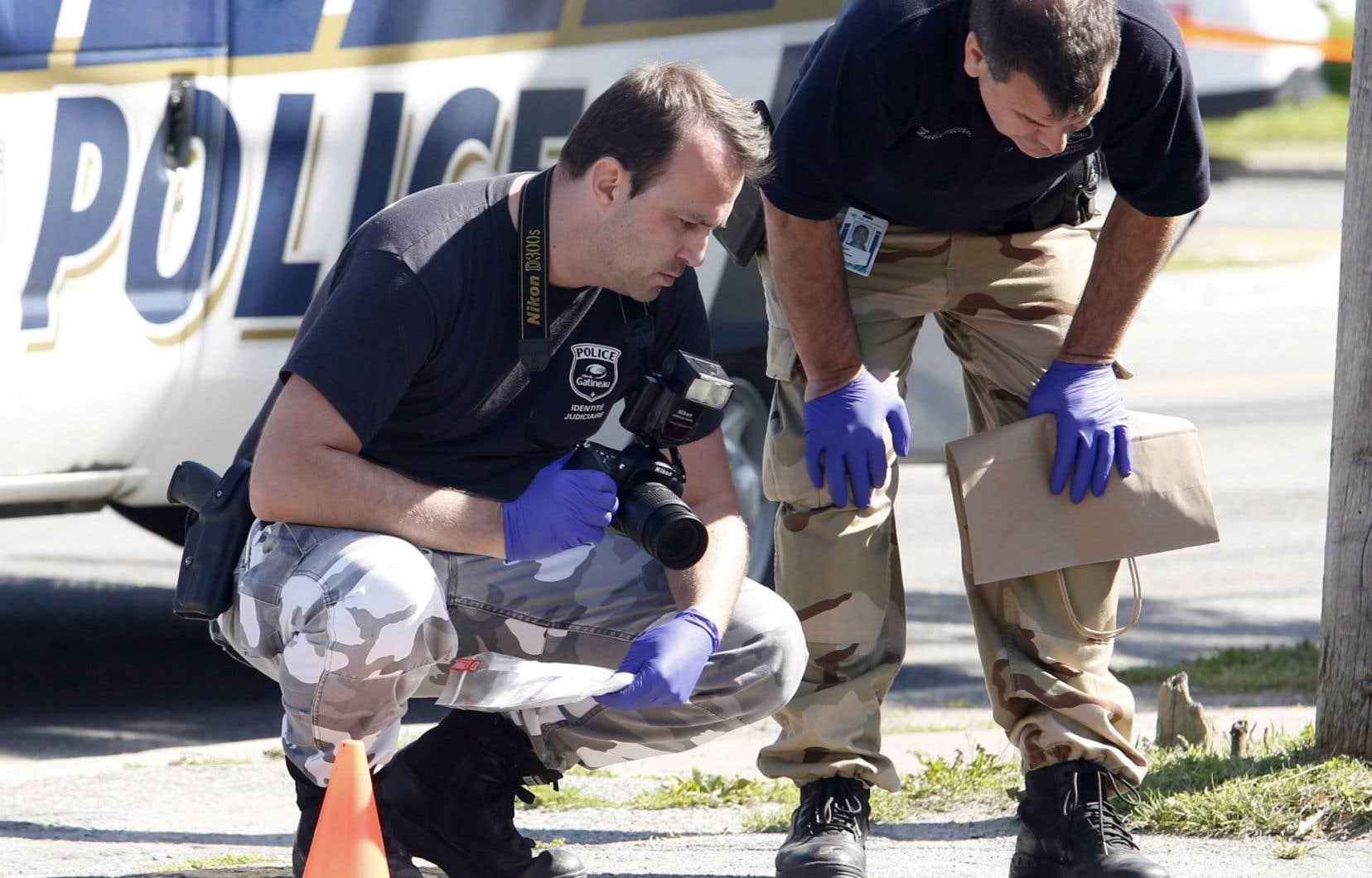 Des policiers examinant une scène où s'est déroulée une fusillade, le 28 août dernier