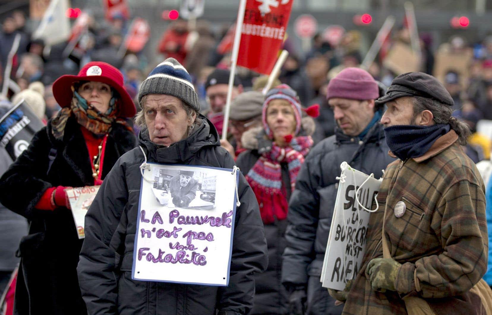 Des gens contestent le plan de réductions budgétaires du gouvernement Couillard, à Montréal.