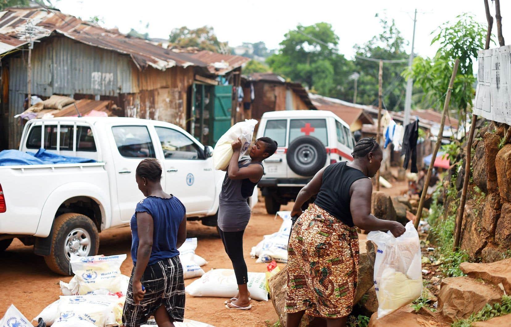 Des citadins en quarantaine reçoivent de l'aide alimentaire en Sierra Leone. Le virus a causé une pénurie de main-d'œuvre dans les champs en pleine période des récoltes.