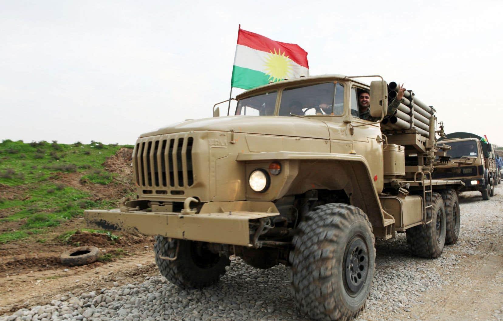 Ces peshmergas revenant du front font le signe de la victoire.