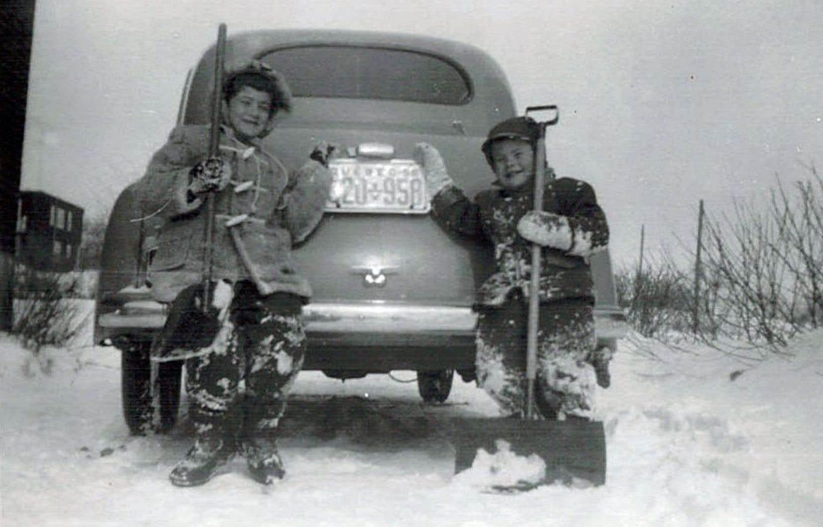 En 1956, Bernard O'Bready, un lecteur du <em>Devoir</em>, pose avec sa soeur,pelle à neige à la main, devant la voiture familiale.