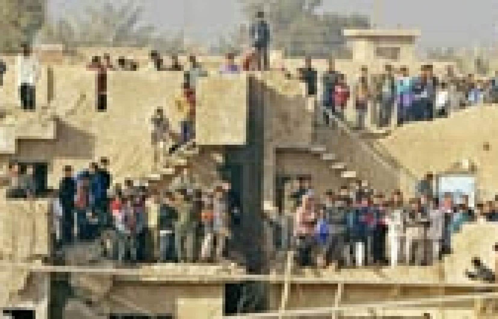 Des Irakiens surveillaient hier les opérations de sauvetage des gardes civils qui ont péri dans l'explosion d'une maison.