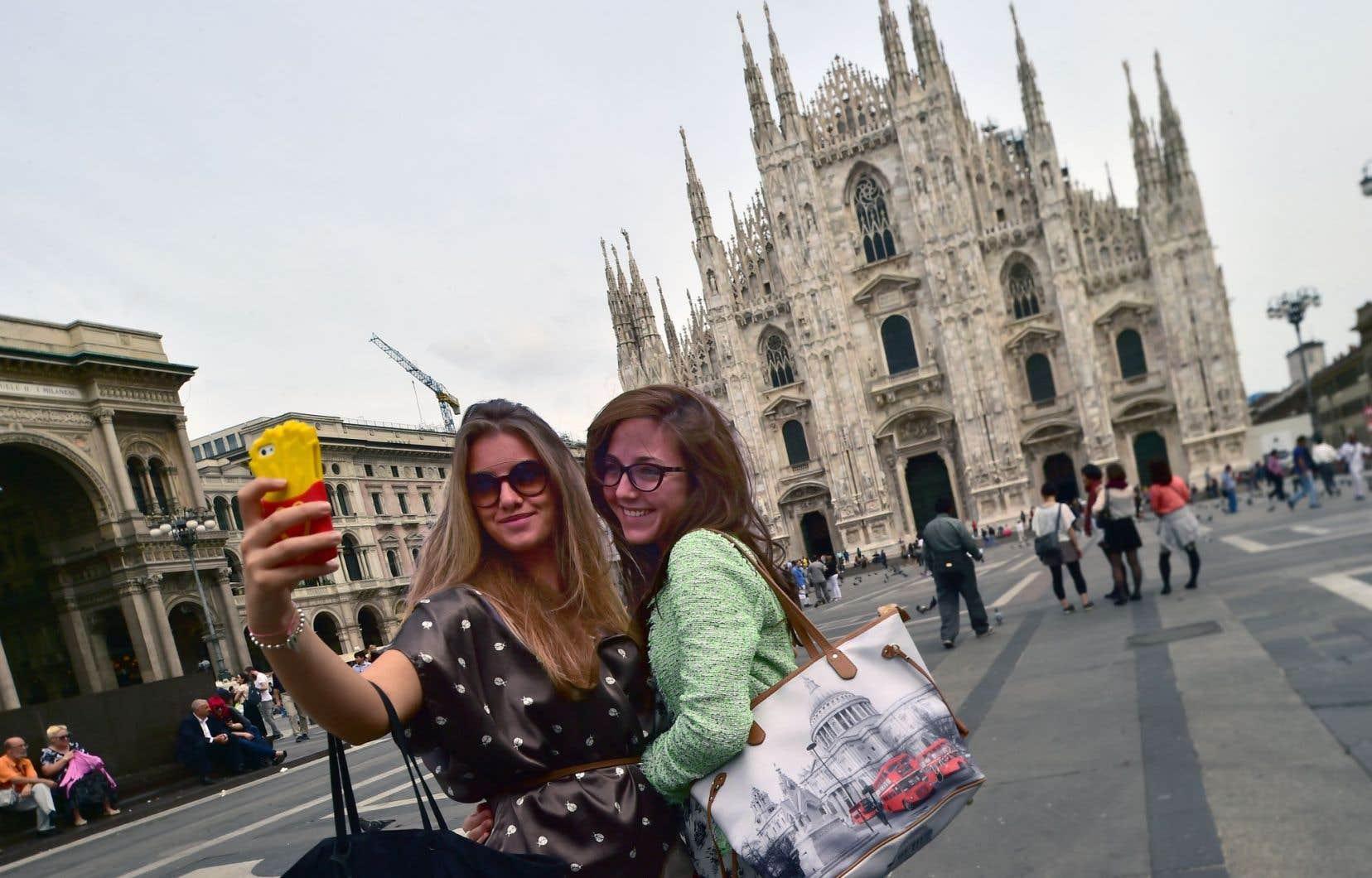 À Milan, deux touristes posent devant la cathédrale. Pour plusieurs, être photographié devant ou dans un lieu est plus important que de le visiter.