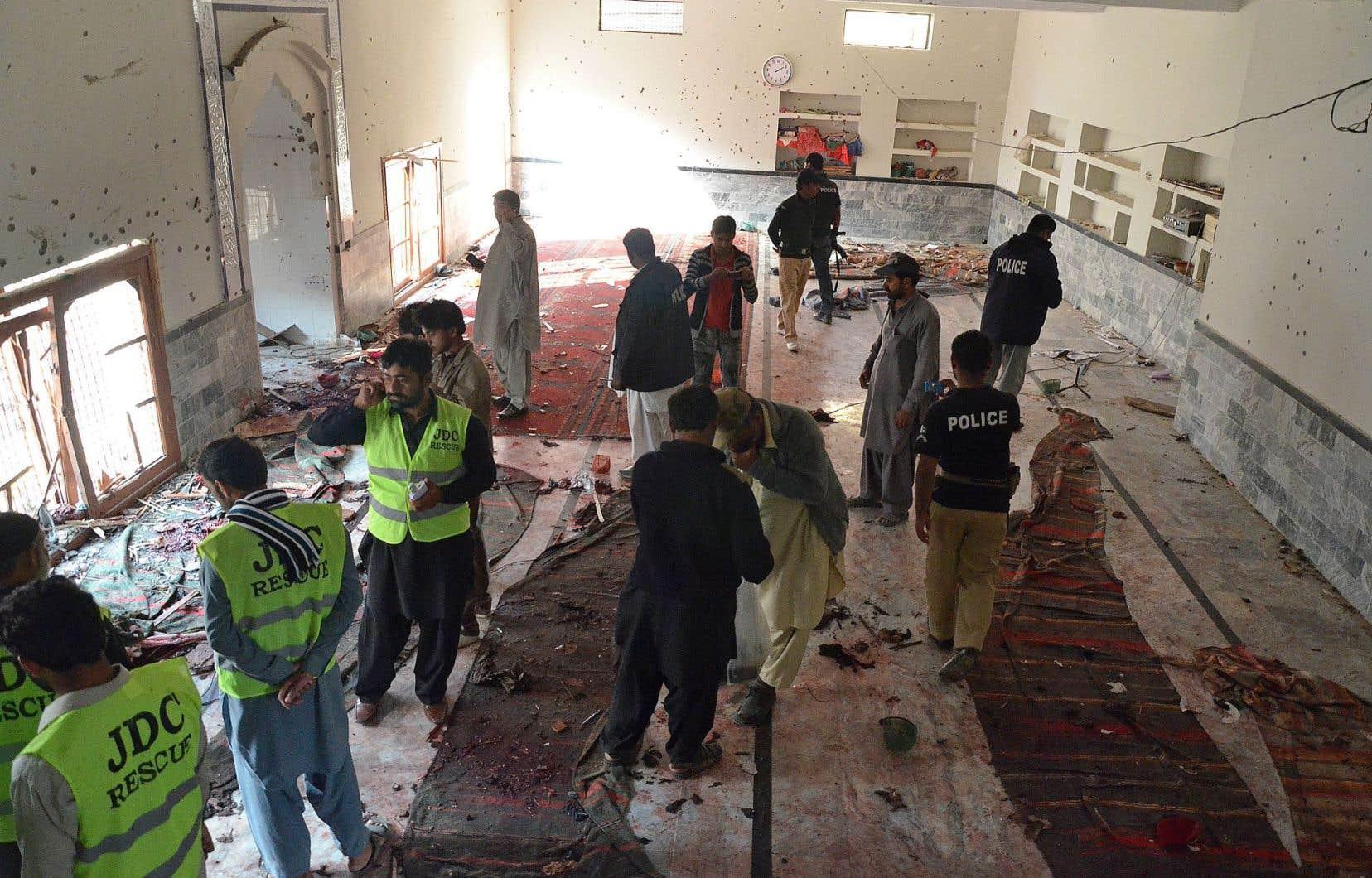 Des agents de la sécurité pakistanaise inspectent la mosquée après l'attaque de vendredi.