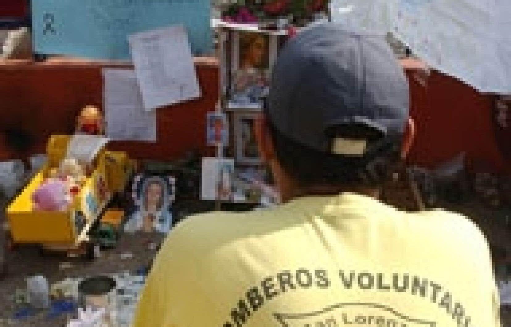Un pompier paraguayen s'est recueilli, hier, devant les objets et les photographies laissés par les gens pour rendre hommage aux victimes de l'incendie qui a fait au moins 440 morts.