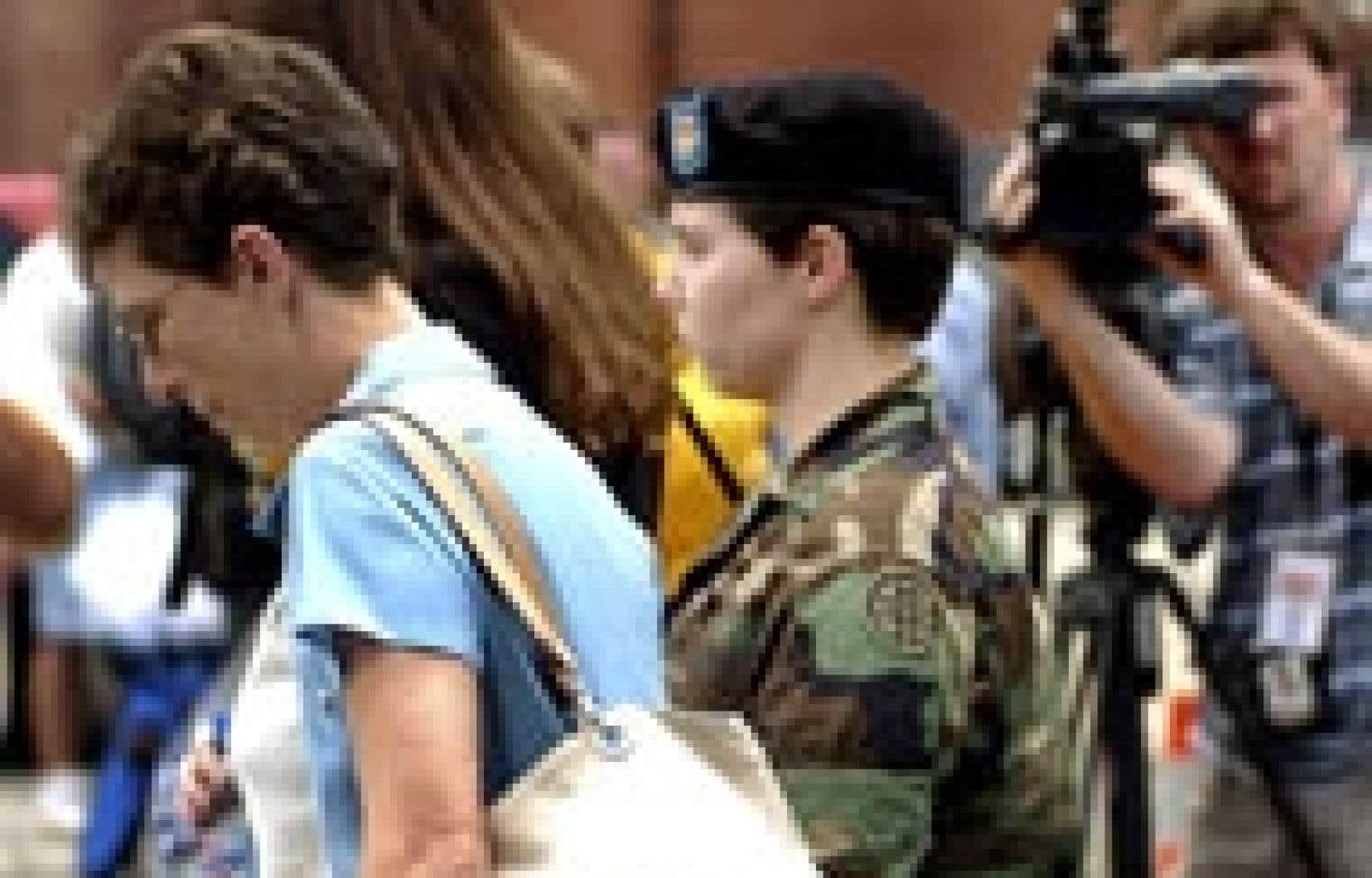 La soldate Lynndie England, qui personnifie le scandale de la prison irakienne d'Abou Ghraïb avec sa photo tenant en laisse un détenu nu, a comparu hier devant une chambre d'accusation militaire devant décider si elle sera jugée par une cour mart