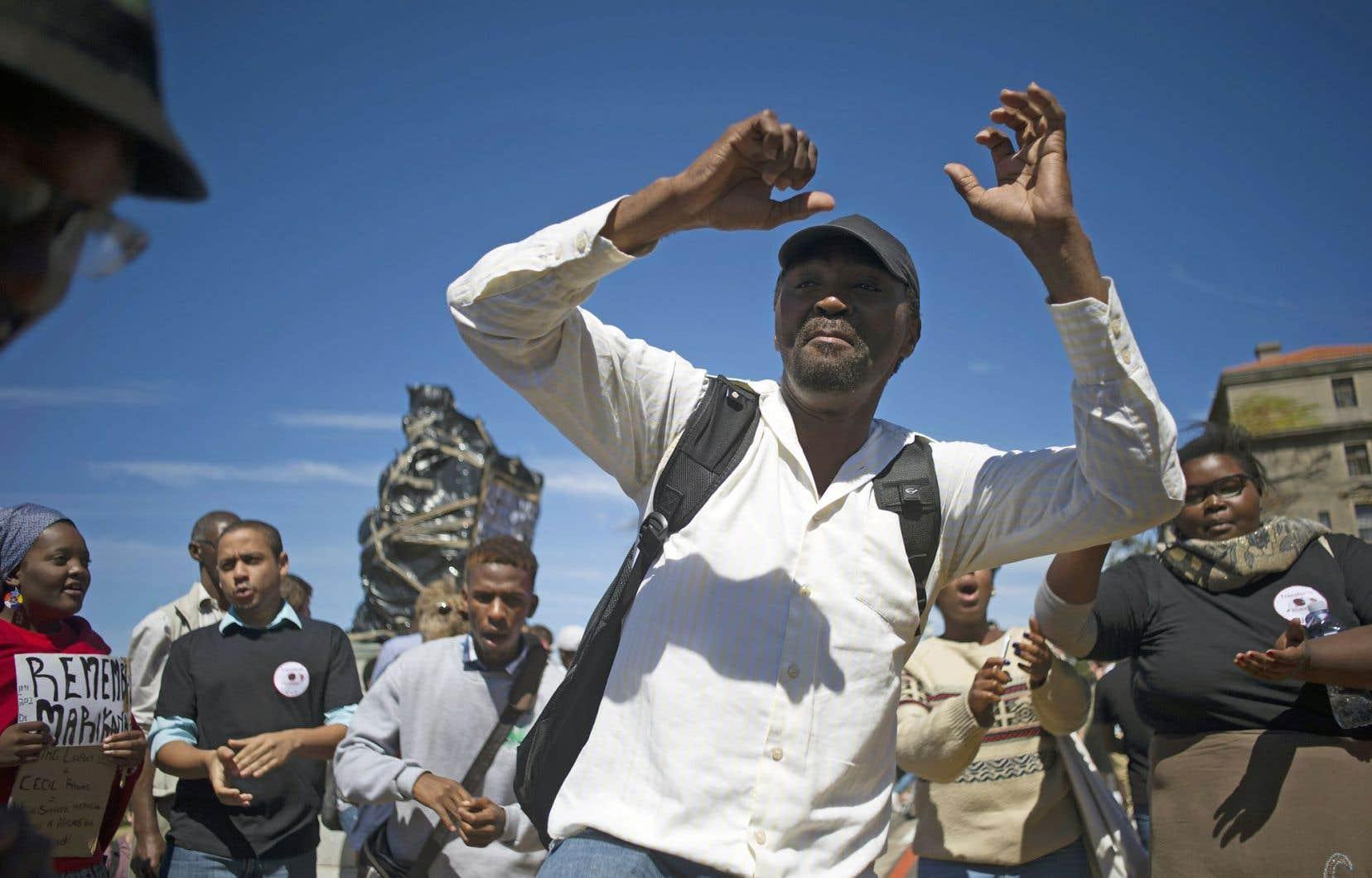 Des étudiants et employés de l'Université du Cap se sont rassemblés, vendredi, devant la statue qu'ils ont recouverte de sacs de plastique et de messages (à l'arrière-plan).