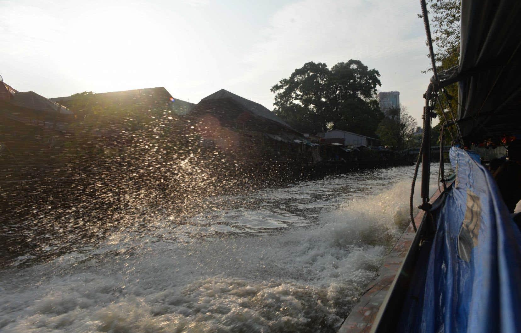 En barque-pirogue sur les canaux de Bangkok, vers Chinatown. Éclats d'eau.
