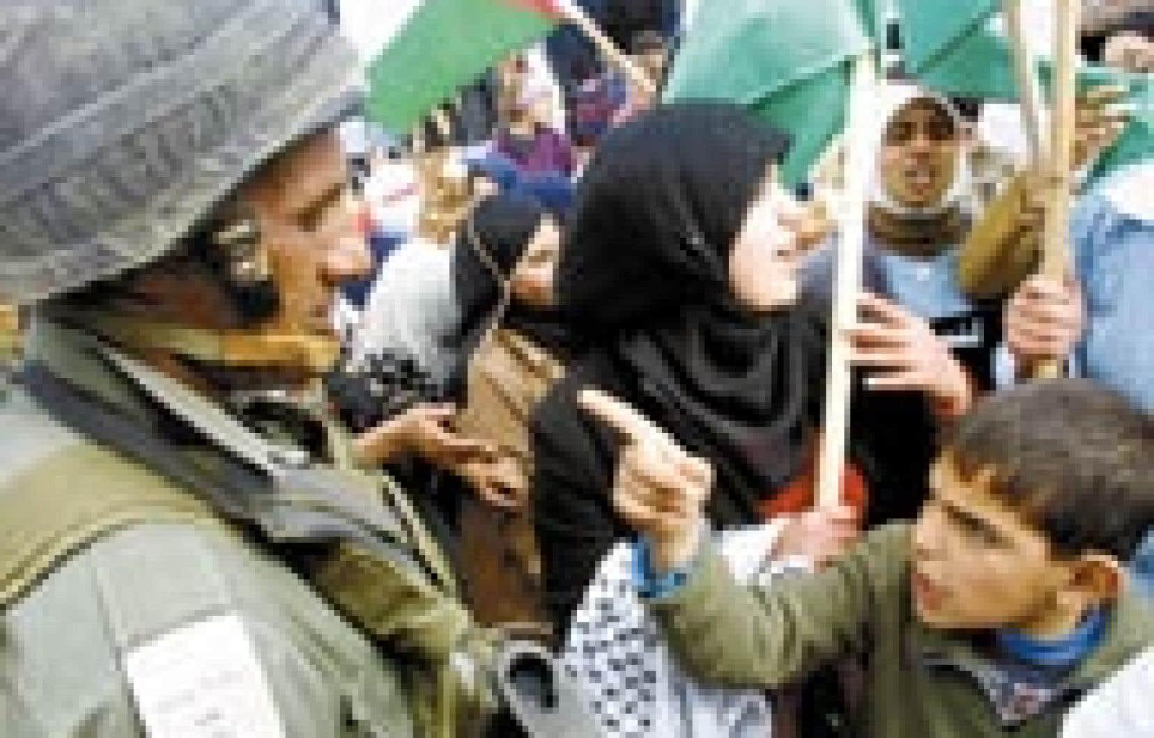 Un enfant palestinien montre un soldat israélien du doigt.