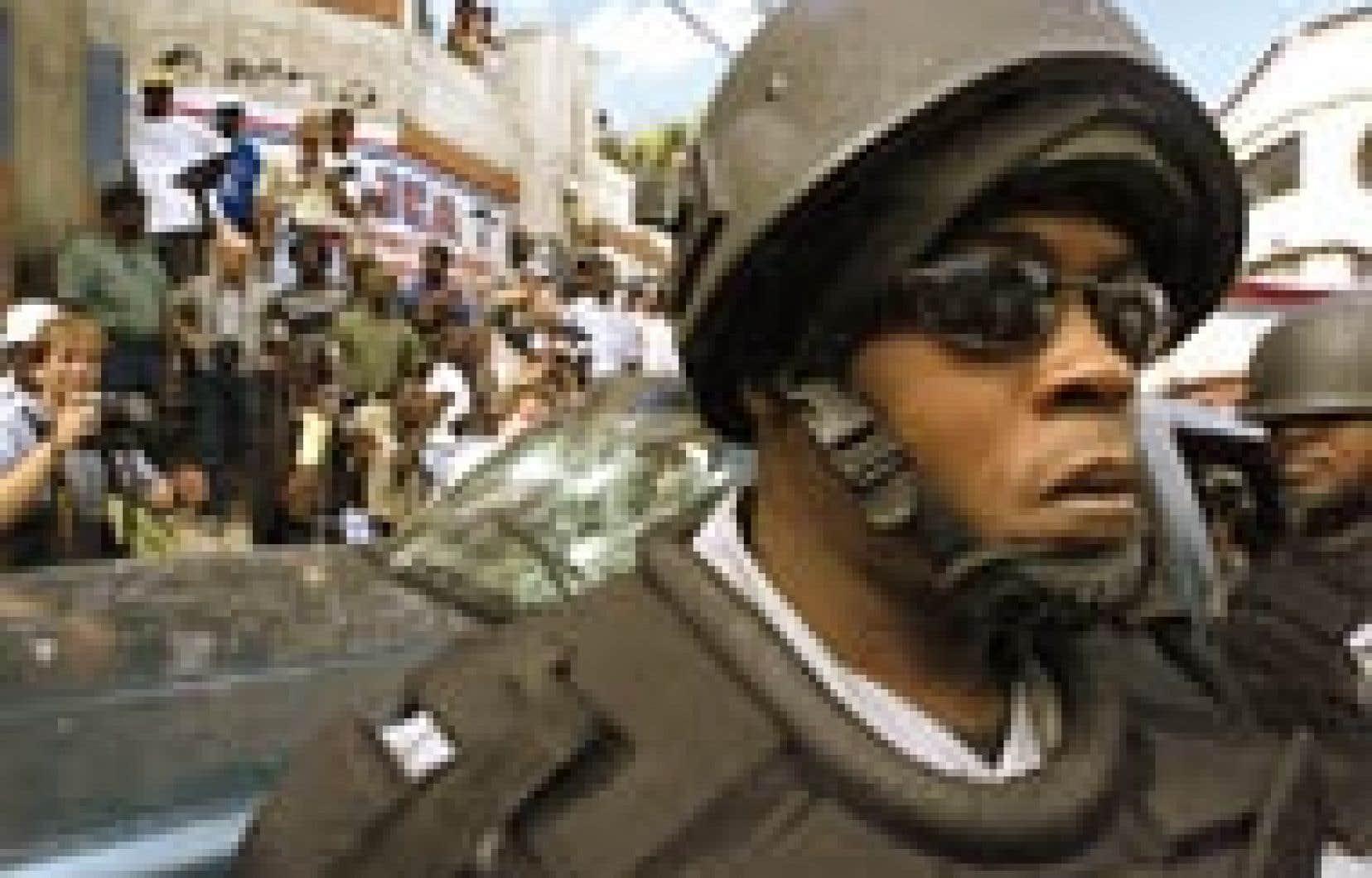 Un policier casqué montait la garde non loin d'un groupe de photographes, dimanche, durant la manifestation des dissidents à Port-au-Prince. La violence croissante inquiète fortement un groupe d'ONG québécoises.