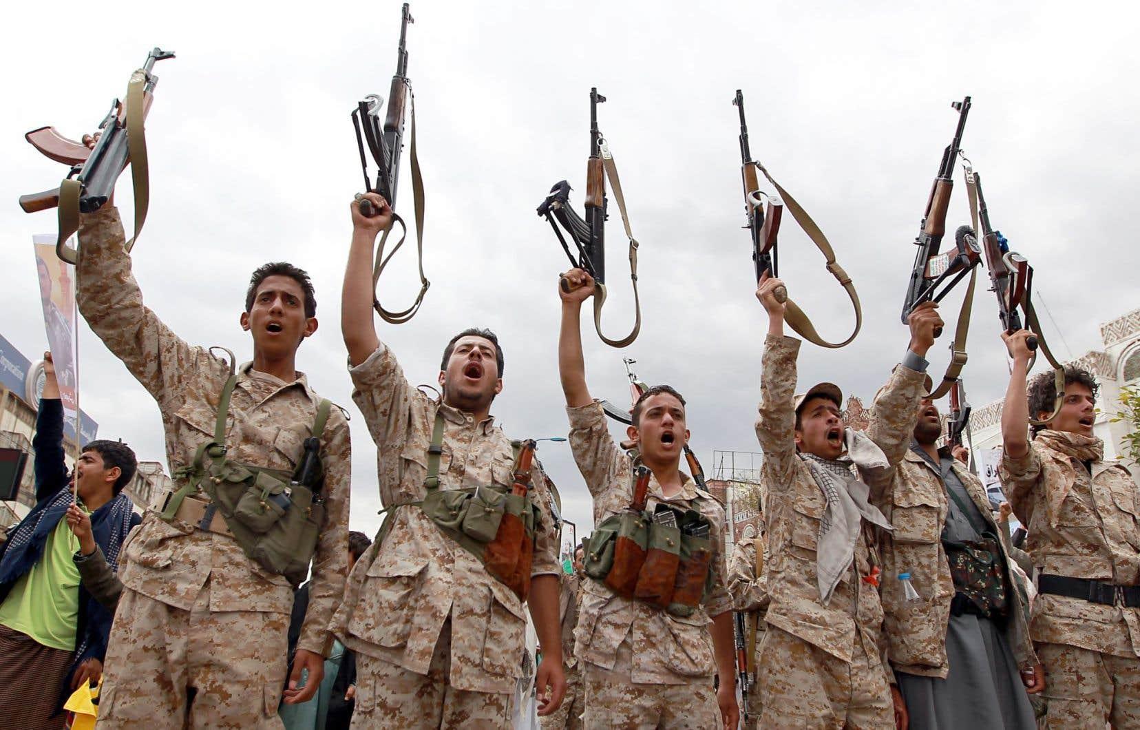 Des Yéménites près des Houthis brandissaient leurs armes jeudi à Sanaa.