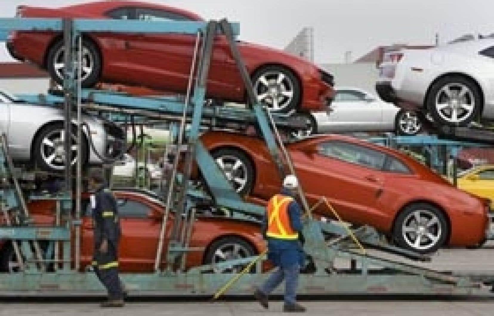 Des ouvriers de l'usine GM d'Oshawa chargent des Chevrolet Camaro sur une remorque afin de  les livrer aux concessionnaires.