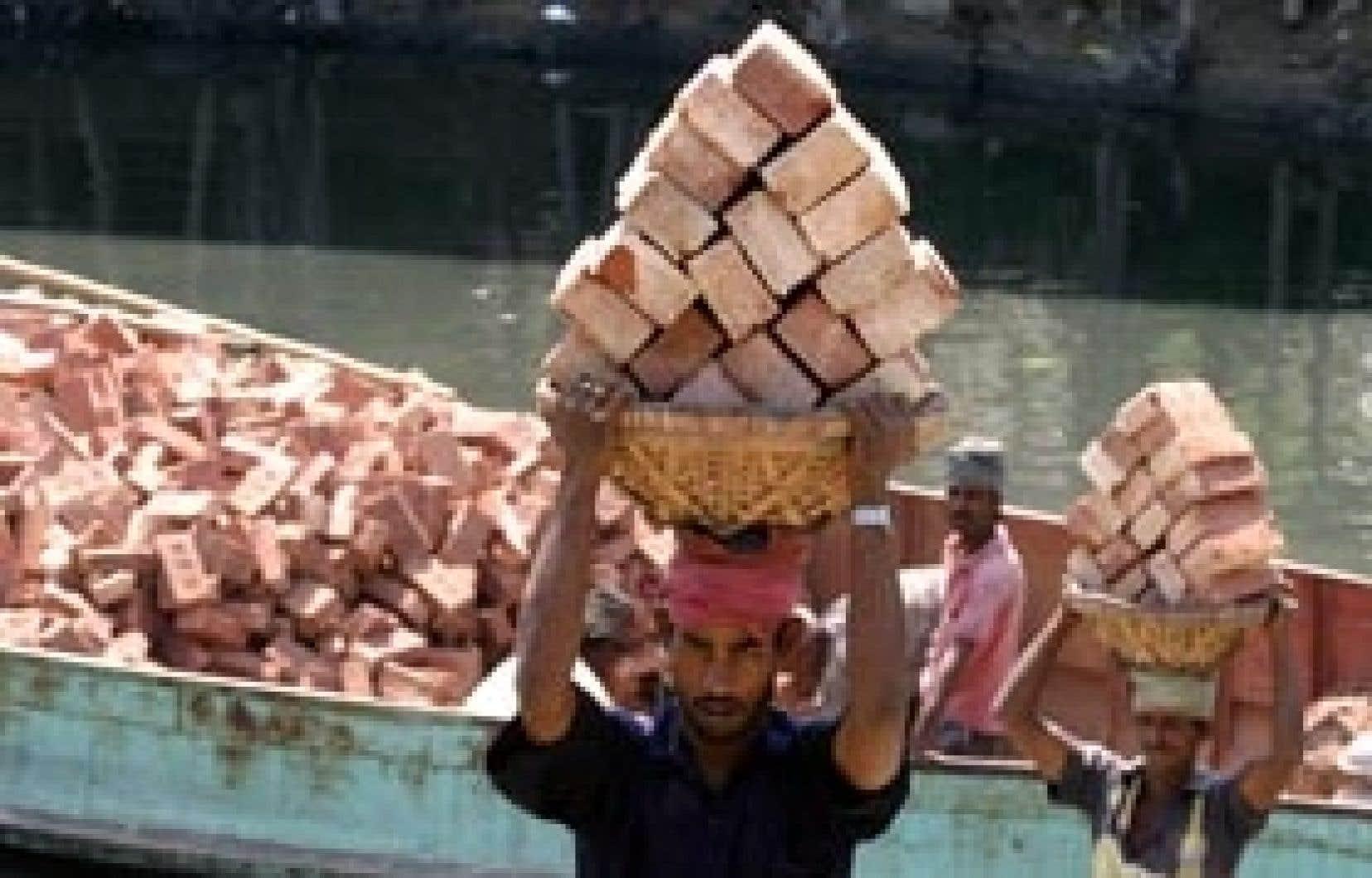 Un travailleur décharge des briques à Dakha, au Bangladesh. Hors activité agricole, le travail informel représente plus des deux tiers des emplois en Asie du Sud et du Sud-Est.