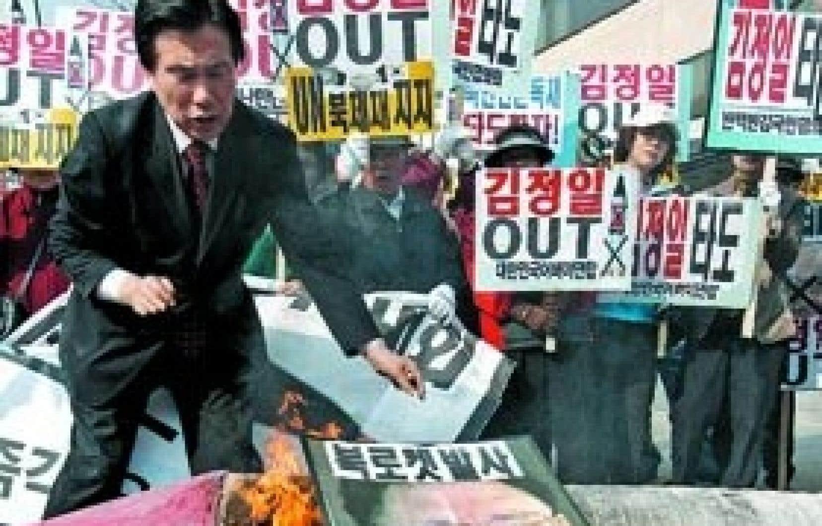 Des manifestants ont brûlé une photo du leader nord-coréen Kim Jong-il, hier à Séoul, en Corée du Sud pour protester contre le lancement par Pyongyang d'une fusée à longue portée.