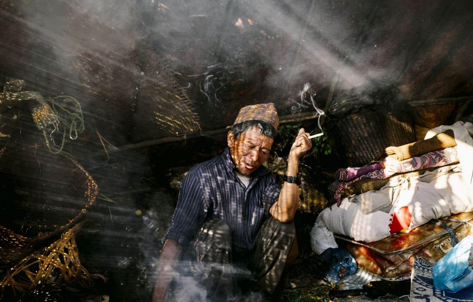 Le père du jeune Anil Gurung, Kam Bahadur, fume sous la tente après avoir pris le thé du matin.