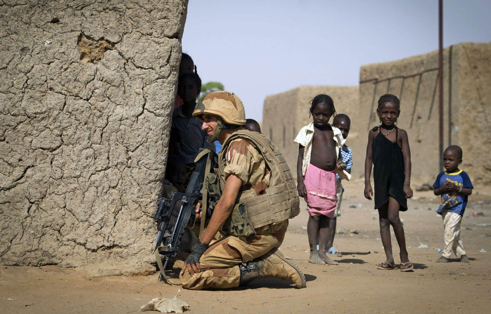 Des enfants surveillent un soldat français à Gao, au Mali, en avril 2005. Dans ce conflit, plusieurs enfants-soldats ont été utilisés par les djihadistes.