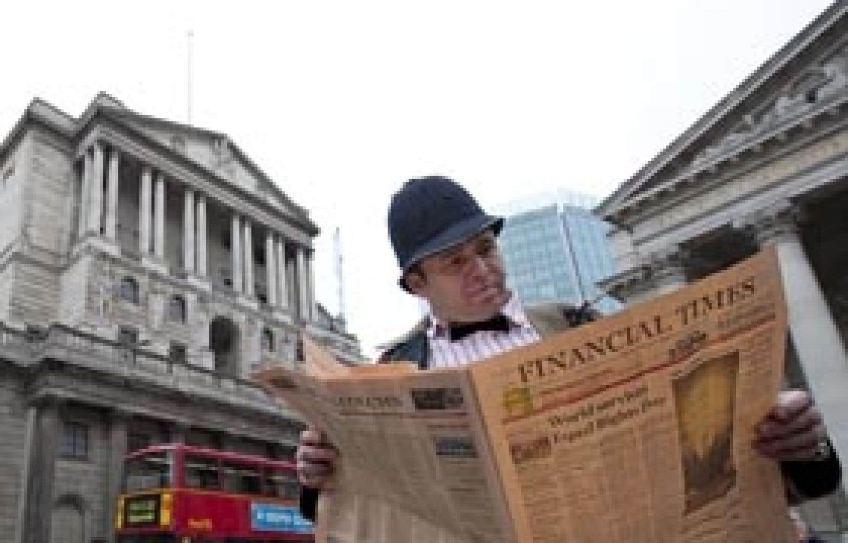 Un manifestant portant cravate et casque policier consulte une fausse édition du Financial Times devant la Banque d'Angleterre.