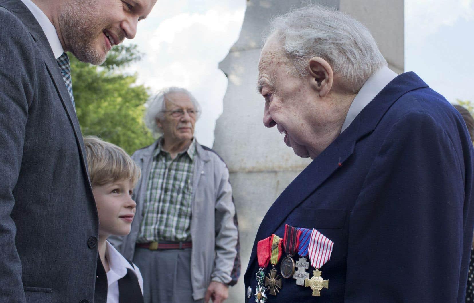 Tristan Malavoy-Racine et son fils saluent Henry Daoulas, dernier survivant de la Résistance française au Québec, devant l'obélisque de l'hôpital Notre-Dame.