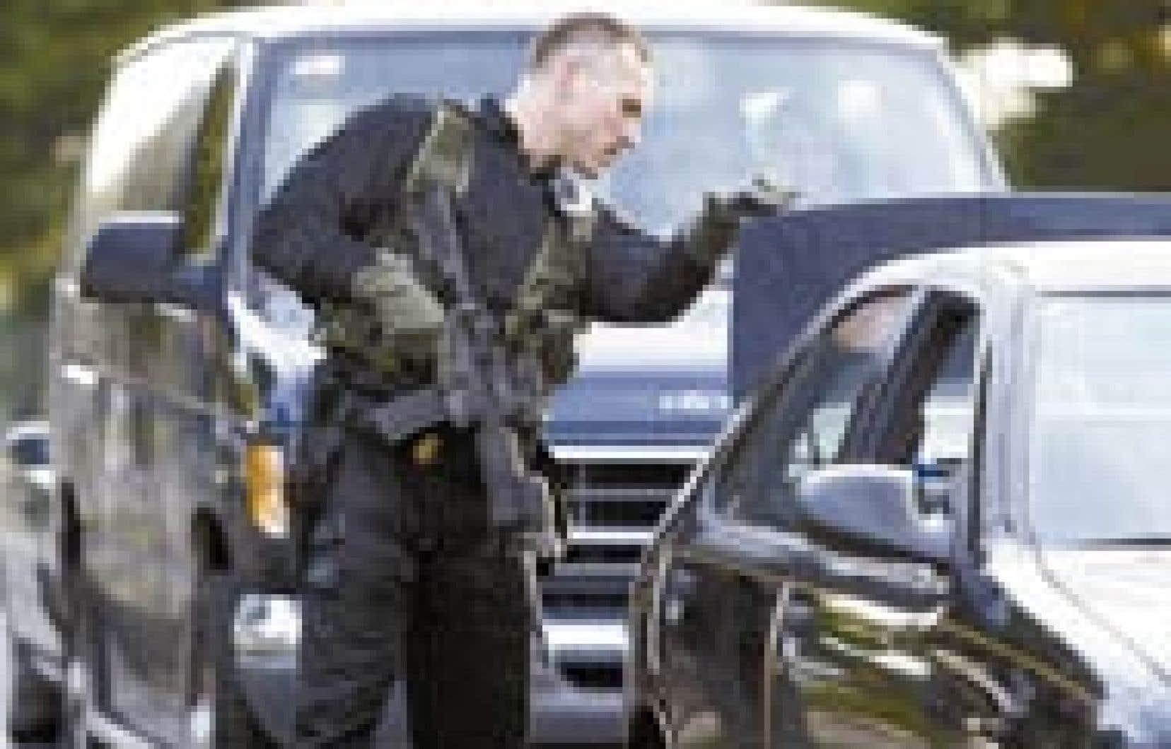 Un policier lourdement armé examine le contenu du coffre d'une voiture à Aspen Hill, au Maryland, où une autre personne a été tuée par un tireur embusqué. — Photo: Chuck Kennedy KRT