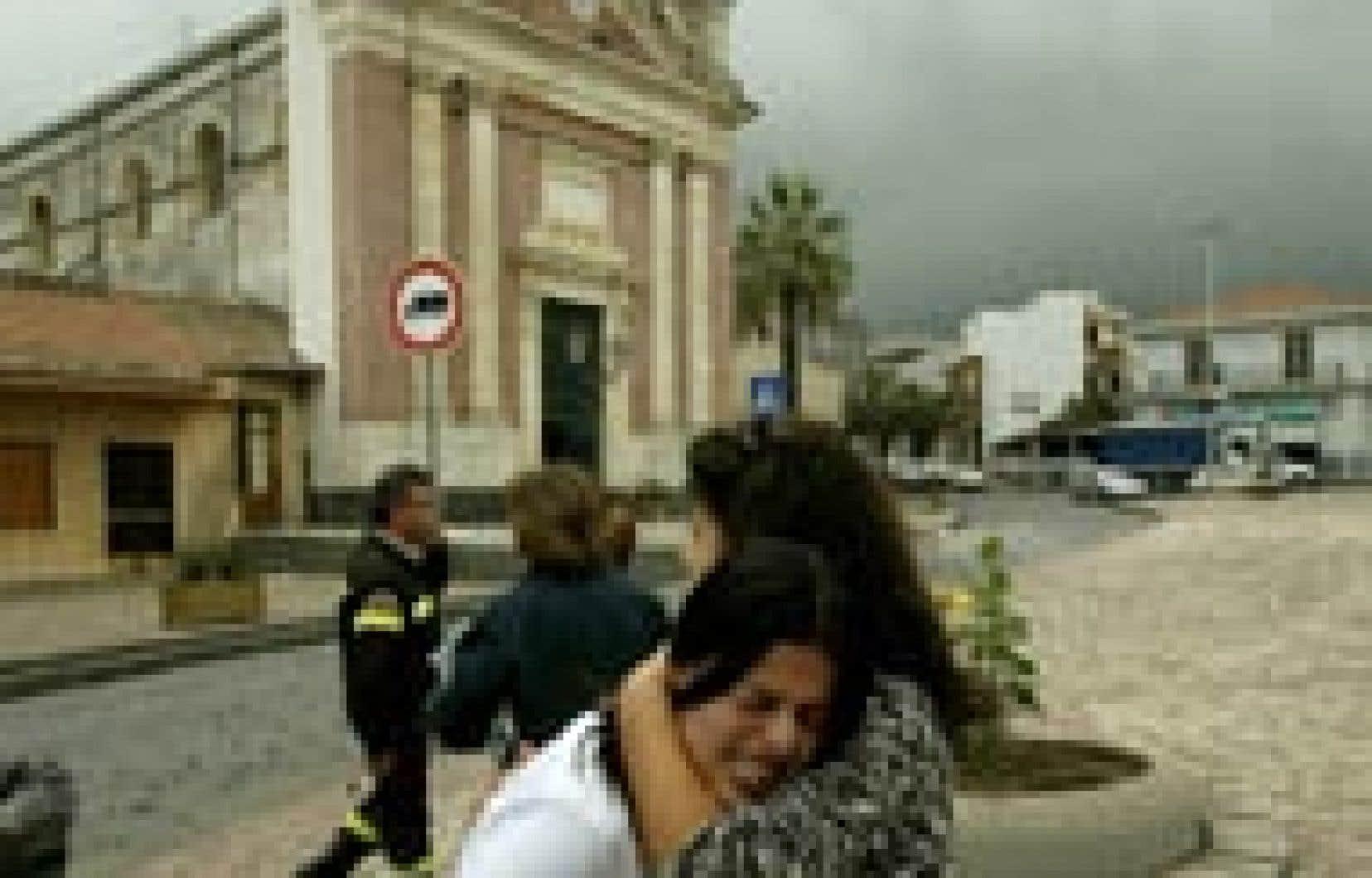 Deux femmes se réconfortent à la suite du tremblement de terre qui a secoué la ville de Santa Venerina, hier. Depuis le réveil, il y a trois jours, de l'Etna, le volcan le plus actif d'Europe, une série de secousses ont frappé l'est de la Sicile, f