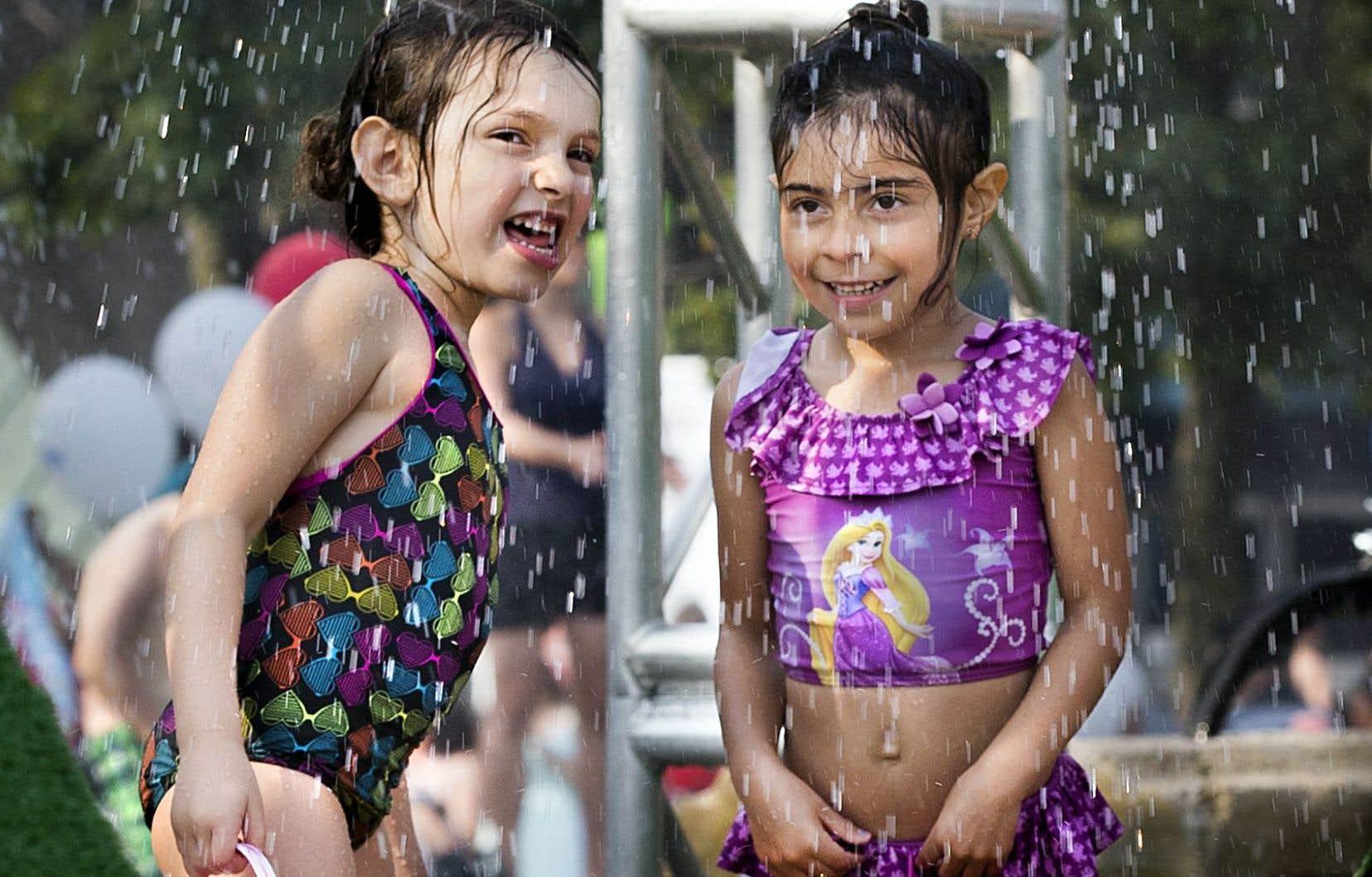 Deux jeunes baigneuses espiègles se rafraîchissaient dimanche à Montréal.