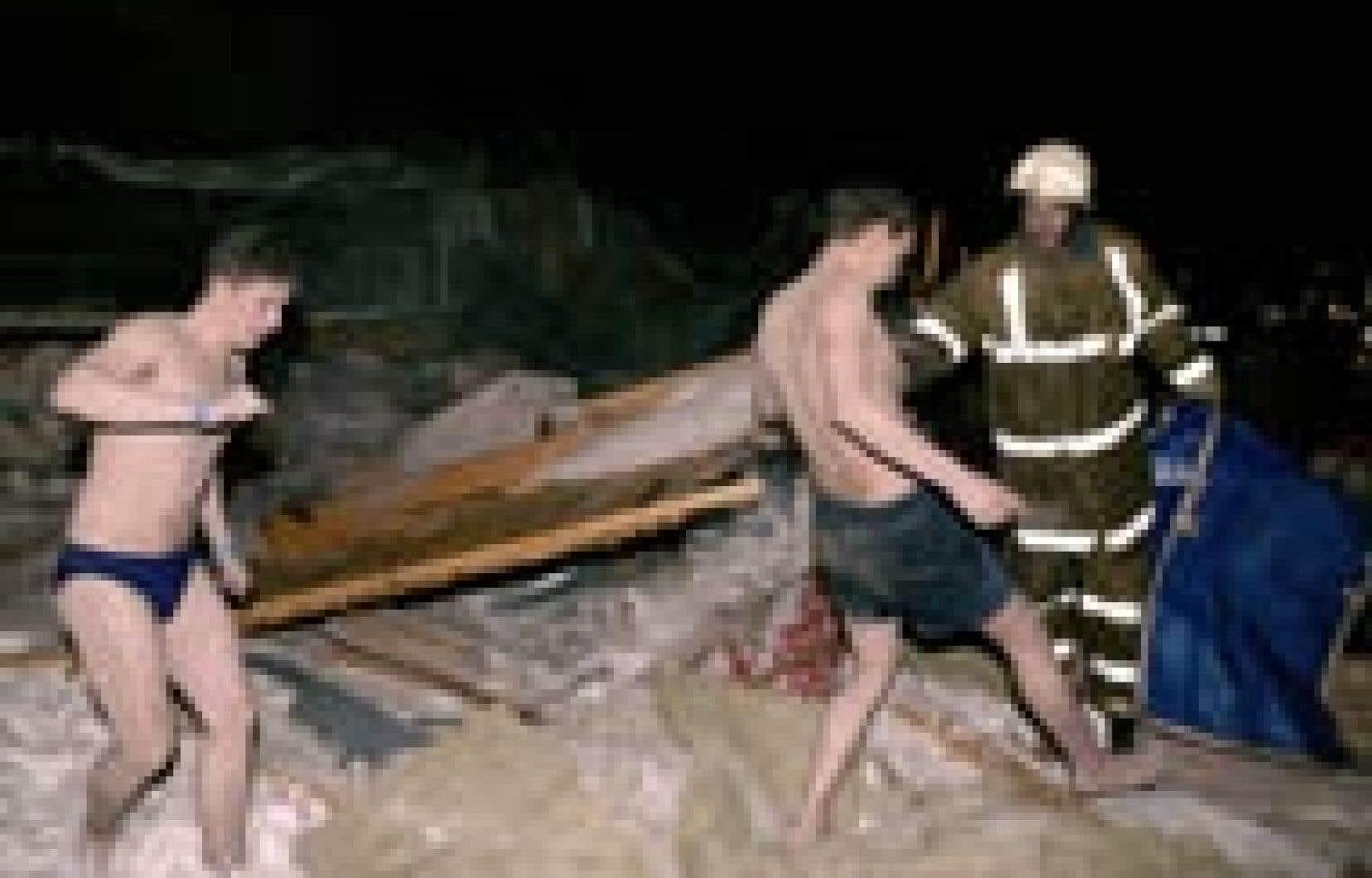 Deux hommes quittent les décombres du parc aquatique de Moscou dont le toit s'est effondré, samedi, faisant au moins 25 morts et une centaine de blessés. Environ 800 personnes se trouvaient dans cet immense centre de loisirs, dont 352 dans la zone a