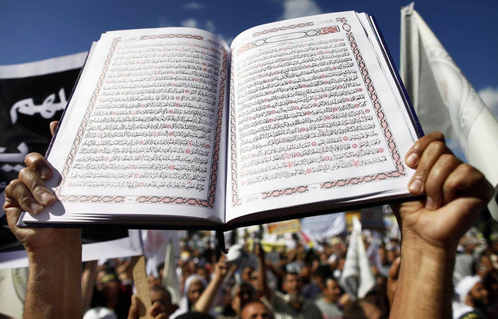 Un manifestant égyptien salafiste brandit des pages du Coran pour demander l'adoption de la charia dans son pays.