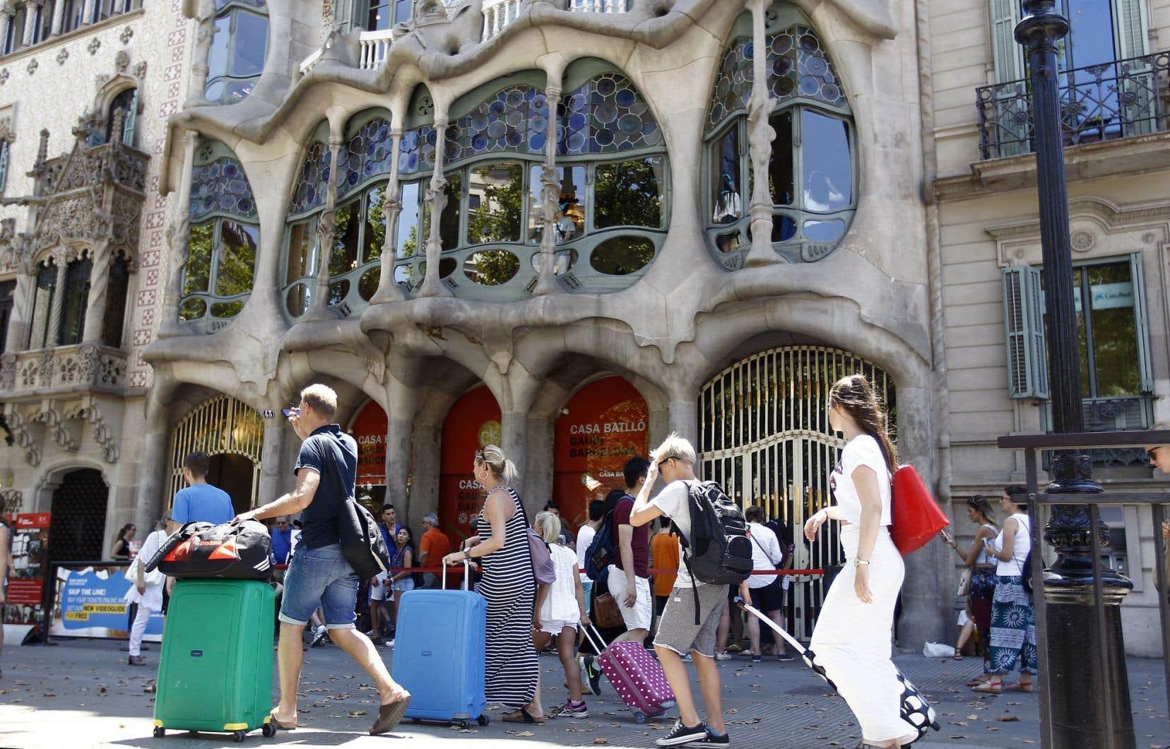 Des touristes circulent devant la Casa Batlló, de l'architecte espagnol Gaudi, à Barcelone.
