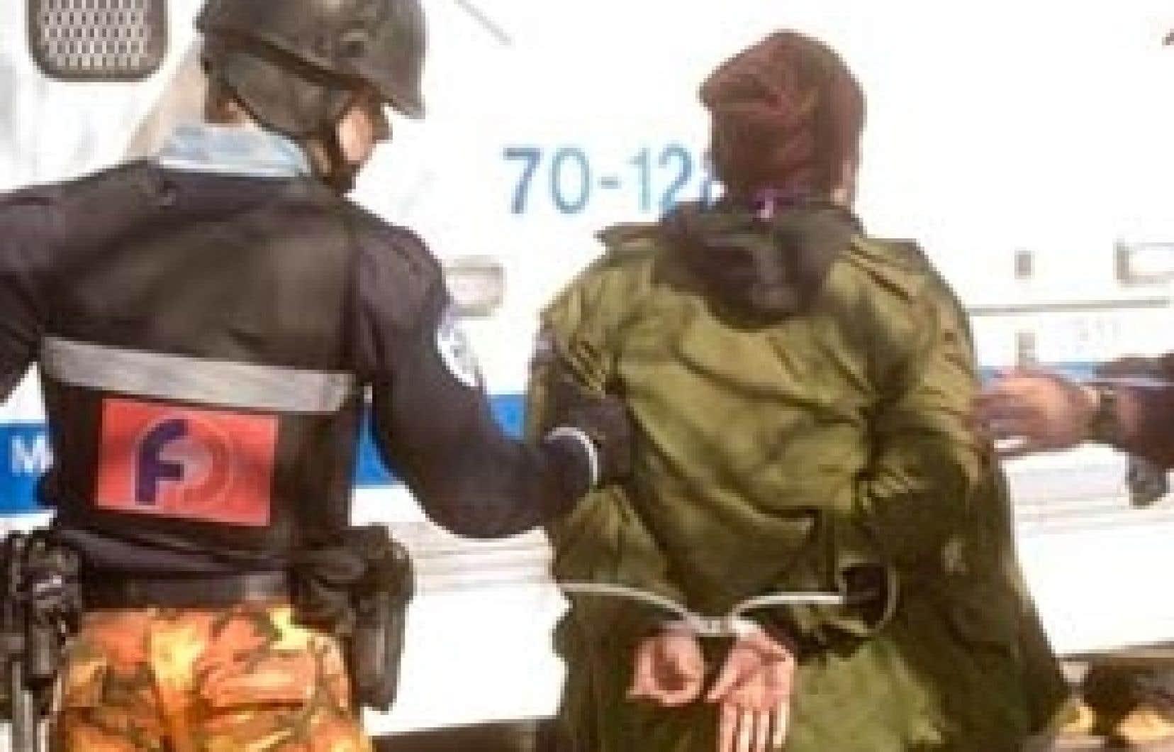 Des policiers procèdent à une arrestation au cours de la manifestation tenue hier à Montréal contre la brutalité policière.