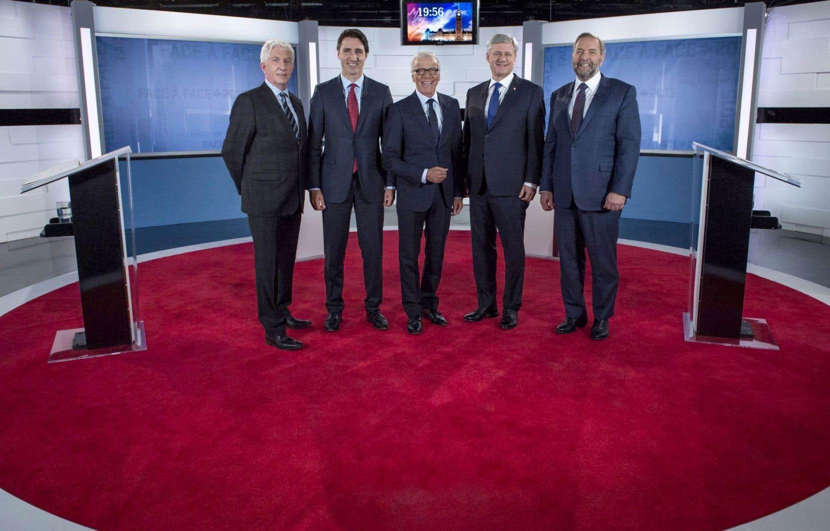 Les quatre chefs qui se sont fait face vendredi soir entourent l'animateur de la soirée. Dans l'ordre: Gilles Duceppe, Justin Trudeau, Pierre Bruneau, Stephen Harper et Thomas Mulcair.