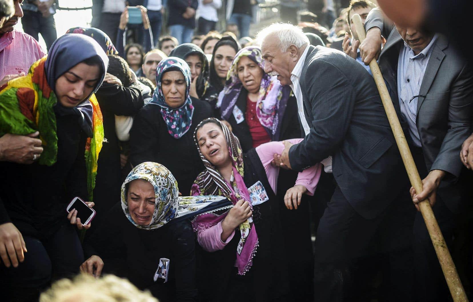 Les proches d'une des victimes pleurent le défunt sur sa tombe deux jours après l'attentat à Ankara.