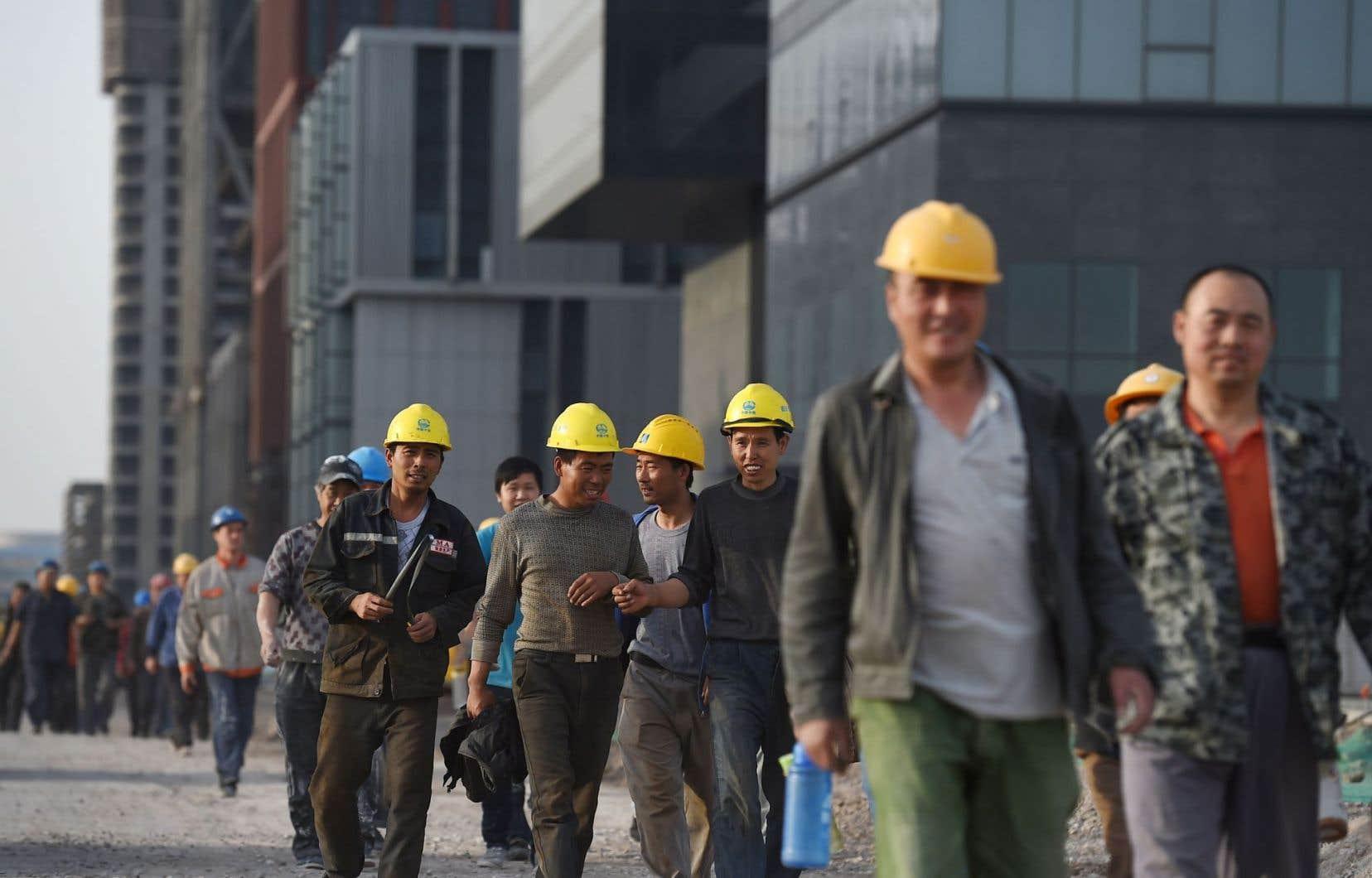 Des travailleurs chinois quittent un chantier après leur journée de travail. La Chine a annoncé une hausse du PIB de 6,9% au troisième trimestre.