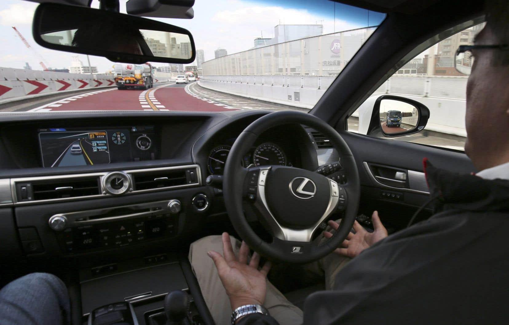 Un employé de Toyota testant, dans les rues de Tokyo, un prototype de voiture autonome.